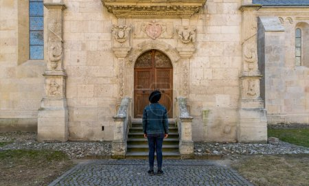 Photo for A tourist young man standing against a beautiful old medieval chatedral door. A man  in front of a an old architecture church entrance door in Alba Iulia, Romania - Royalty Free Image