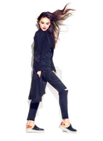 Photo pour Belle fille modèle posant dans des vêtements à la mode. Belle jeune femme brune en tenue tendance, maquillage de mode et accessoires isolés sur fond blanc. Style urbain, noir total - image libre de droit