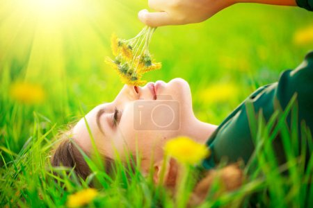 Photo for Beautiful young woman lying on the field in green grass and smelling blooming dandelions. Allergy free concept - Royalty Free Image