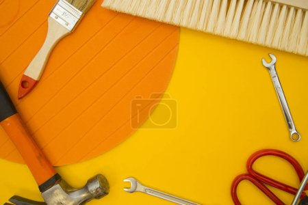 Repair and renovation concept. A set of tools for repair with brushes, screwdriver, gloves on a yellow background top view, flat lay, copy space