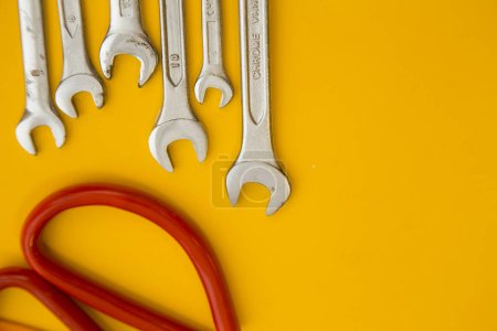 Repair and renovation concept. A set of metal tools for repair with wrench on a yellow background top view, flat lay, copy space