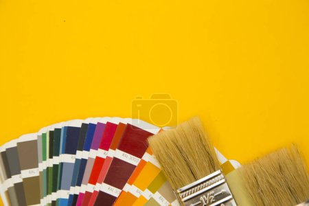 Repair and renovation concept. A set of tools for repair with brushes, color palette on a yellow background top view, flat lay, copy space