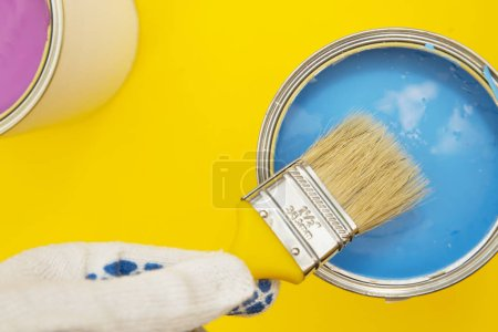 Repair and renovation concept. A set of tools for repair with cans of paint, brushes on a yellow background top view, flat lay, copy space