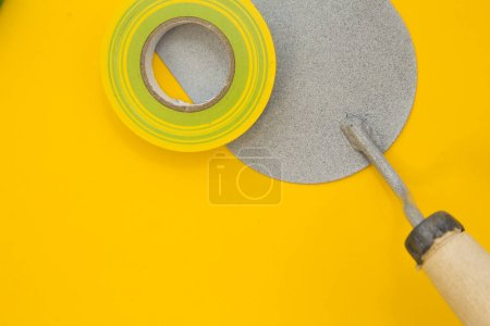 Repair and renovation concept. A set of tools for repair with insulating tape on a yellow background top view, flat lay, copy space