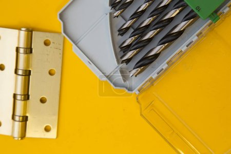 Repair and renovation concept. A set of metal tools for repair with drills, wrench and pliers on a yellow background top view, flat lay, copy space