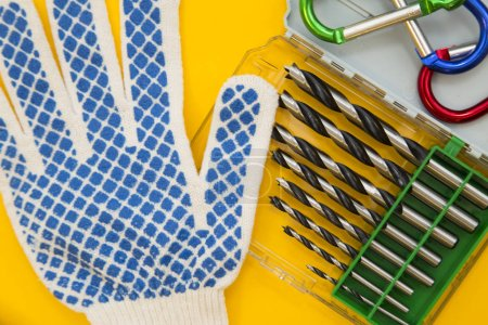 Repair and renovation concept. A set of metal tools for repair with drills, gloves, wrench and pliers on a yellow background top view, flat lay, copy space