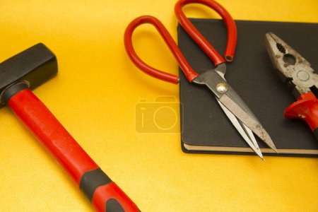 Repair and renovation concept. A set of metal tools for repair with hammer, wrench and pliers on a yellow background top view, flat lay, copy space