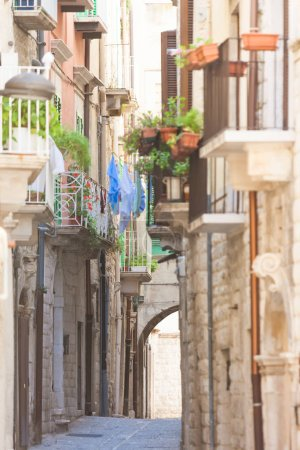 Photo for Molfetta, Apulia, Italy - Old balconies and a historical archway in an alleyway of Molfetta - Royalty Free Image