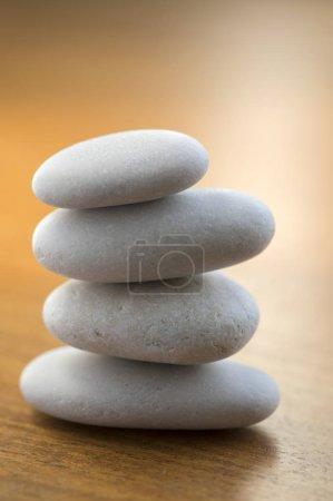 Photo pour Quatre tour de cairn de pierres, pierres de poise, rock sculpture zen, galets blancs lumineux sur fond en bois - image libre de droit