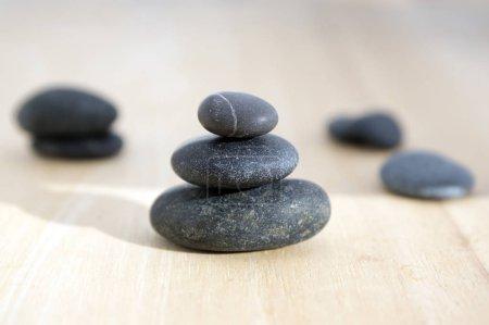 Harmonie et équilibre, pierres poise sur table en bois, noir cailloux en plein soleil