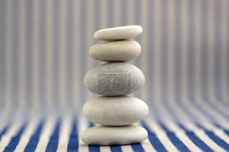 Photo pour Harmonie et équilibre, cairn de roche de galets, pierres de poise simple sur fond rayé blanc et bleu, sculpture zen rock, cinq petits cailloux blancs, seule tour, simplicité - image libre de droit