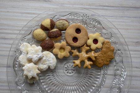 Photo pour De nombreux types de biscuits de Noël sur plaque transparente en verre coupé, des aliments sucrés sur table en bois, partiellement occupé - image libre de droit