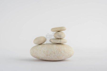 Photo pour Un cairn de pierres de simplicité isolé sur fond blanc, groupe de cinq cailloux blancs en tour, harmonie et équilibre - image libre de droit