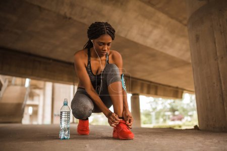 African american woman runner in sportswear tightening shoe lace