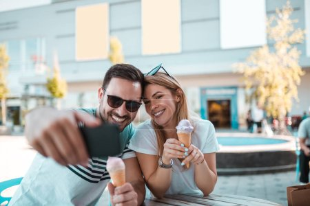 Photo for Young man with sunglasses is taking selfie with his girlfriend while they having ice-cream outdoors - Royalty Free Image