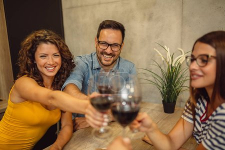 Photo for Cheers! Group of friends having fun, drinking wine and cheers - Royalty Free Image