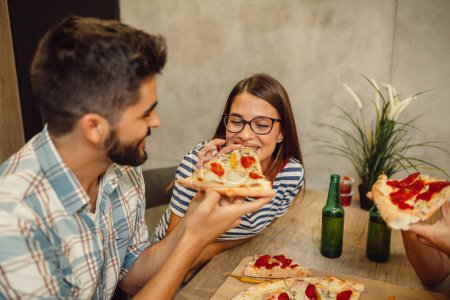 Photo for Young couple drinking beer and enjoying pizza together - Royalty Free Image