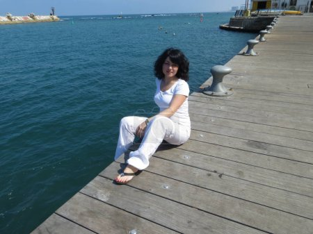 Young brunette girl in a white suit sits on a pier near the sea in Israel in Jaffa