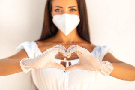 Photo pour Fille dans un masque blanc N- 95 sur le fond d'un mur blanc. La fille montre le geste - le cœur. Comme un signe d'amour partout dans le monde . - image libre de droit