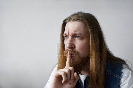 Photo pour Silence, secret et concept de conspiration. Photo d'un Européen aux yeux bleus non rasé veston en denim tenant un doigt sur ses lèvres, disant Chut, demandant de garder quelques informations confidentielles un secret - image libre de droit