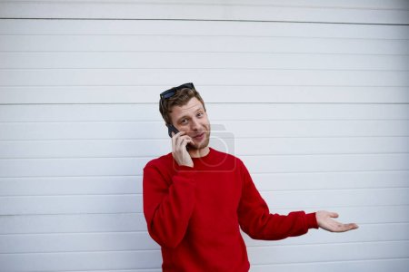 Photo for Candid shot of handsome young European man with stubble shrugging shoulders while talking on mobile phone to his girlfriend, looking clueless, gesturing and saying: I don't know, So what, Who cares - Royalty Free Image