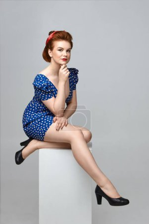 Photo for Coquettish confident young lady wearing stylish vintage clothes and accessories posing sitting on cube in studio with hand on chin. - Royalty Free Image