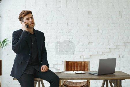Foto de Apuesto seguro joven caucásica empresario hablando por teléfono móvil, sentado en el escritorio en la oficina - Imagen libre de derechos