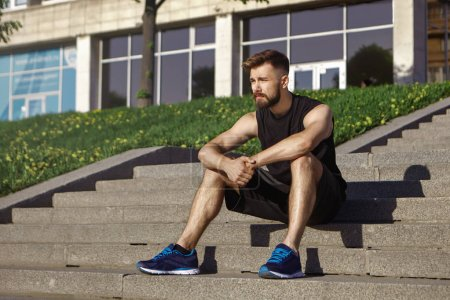 Photo for Summer portrait of attractive fashionable young male jogger with stubble enjoying sunny summer weather in city, having rest on steps. - Royalty Free Image