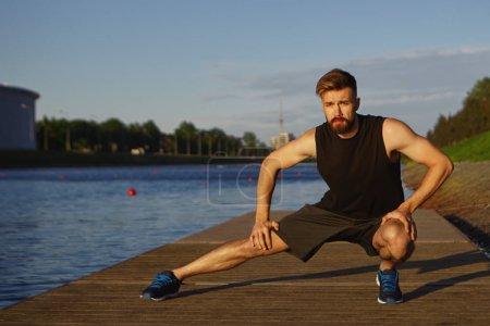 Photo pour Attrayant jeune barbu guy formation par rivière, étirement des jambes, faire des plongées latérales . - image libre de droit