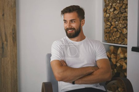 Photo for Positive friendly young man with muscular body, thick beard and stylish haircut posing indoors, sitting in rustic interior, crossing arms on chest and smiling. - Royalty Free Image