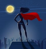 Super Girl Superhero stands on roof of skyscraper and looks at night city
