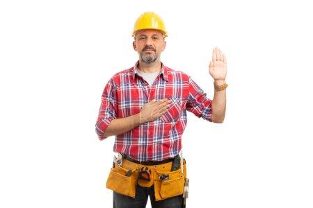 seriöser Bauunternehmer, der mit einer Hand nach oben und der anderen Hand auf Herz schwört, isoliert auf weißem Studiohintergrund