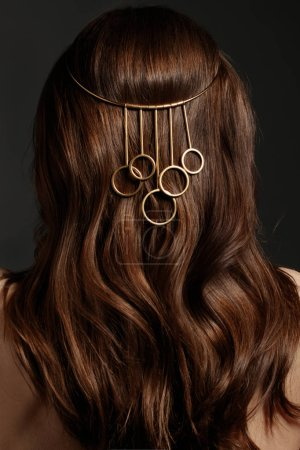 Brunette model with curly hair style and golden jewelry on head, rear view