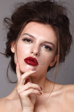 Portrait of beautiful glamorous brunette woman with bright make up and stylish hairdress. Red lips