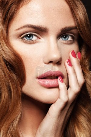 Photo for Close up portrait of beautiful female model with pink lips and wavy hair touching her face - Royalty Free Image