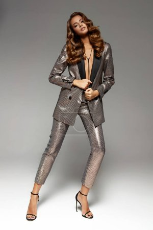 fashion studio portrait of attractive young woman with tanned skin and glamour make up wearing shiny suit and heels, full length