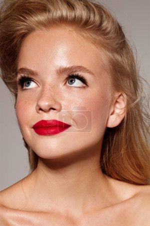 Foto de Labios rojos. Chica joven modelo con estilo de cabello rubio y piel de la belleza. Maquillaje perfecto. - Imagen libre de derechos