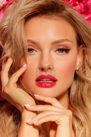 Photo pour Portrait de belle mannequin blonde aux yeux bleus et lèvres rouges sur fond floral, concept de maquillage de mariage - image libre de droit