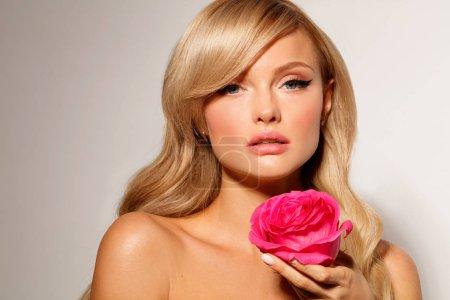 Photo pour Portrait de la belle blonde mannequin avec une rose rouge sur fond clair - image libre de droit