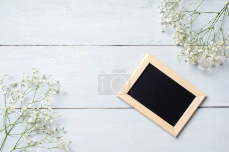 Framework for photo or congratulation on blue rustic wooden desk with flowers. Spring background, banner mockup for Womens or Mothers Day, Easter, spring holidays. Flat lay, above view.