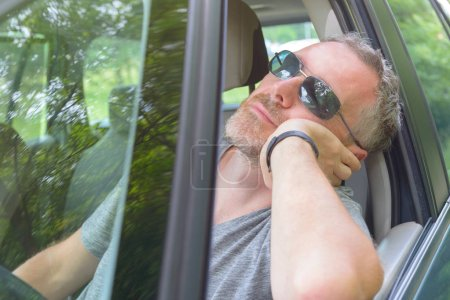 Man driver is resting in the car during a travel break
