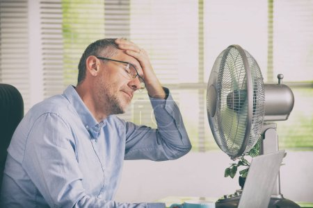 Photo for Man suffers from heat while working in the office and tries to cool off by the fan - Royalty Free Image