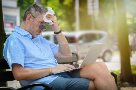 Man suffers from heat while working with laptop outside and wiping his forehead with tissue