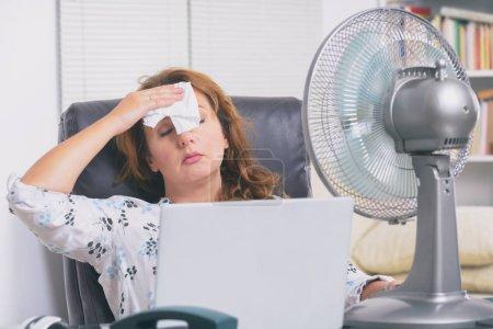 Mujer sufre de calor mientras trabaja en la oficina y trata de refrescarse por el ventilador