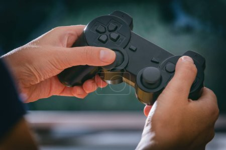 Mature woman or wife plays video game using the gamepad at home