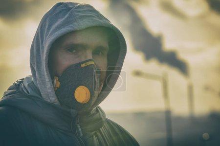 Photo pour Homme portant un véritable masque anti-pollution, anti-smog et virus ; smog dense dans l'air - image libre de droit