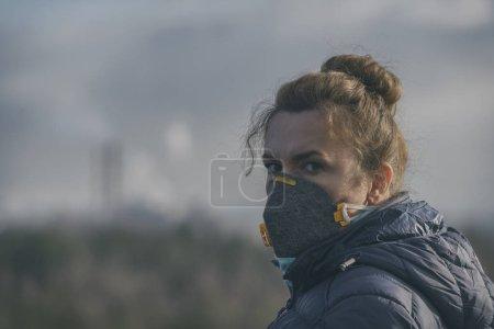 Femme portant un véritable masque anti-pollution, anti-smog et virus ; smog dense dans l'air.
