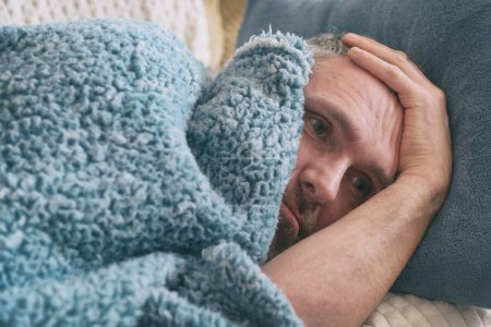 Photo for Mature man suffering from depression lies sadly covered with a blanket on his bed - Royalty Free Image