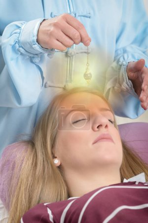 Alternative medicine therapist using pendulum to m...