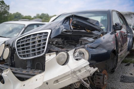 The front end of a car that has been mangled beyond repair in a car accient, the bumper tied on with string